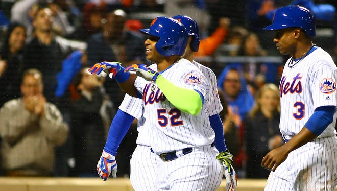 Mets centerfielder Yoenis Cespedes is congratulated after hitting a grand slam in the third inning at Citi Field.