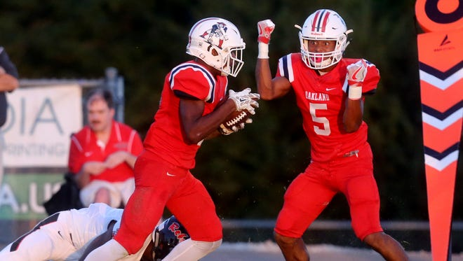 Oakland's Jalen Locklayer (3) intercepts a pass intended for Maryville's AJ Davis (3) as Locklayer's teammate Woodi Washington cheers him during the game on Friday, Aug. 25, 2017, at Oakland.