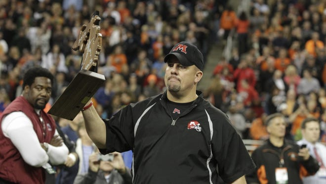 Muskegon Head Coach Shane Fairfield accepts the runner up trophy after their MHSAA Division 2 Championship Game loss against the Birmingham Brother Rice Warriors on Friday, Nov. 29, 2013 at Ford Field in Detroit. Brother Rice won the game 38-21 and finishes the season with both an undefeated record and the Division 2 State Championship trophy. Jarrad Henderson/Detroit Free Press