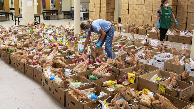 Volunteers at the Southeast Asian Coalition of Central Massachusetts pack boxes with food  Friday in Worcester.
