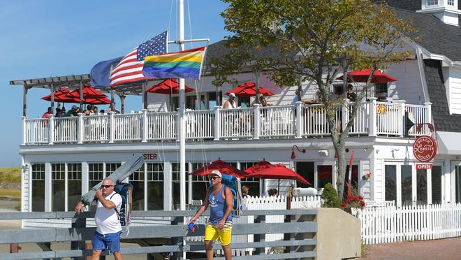 Two men walk over the bridge on Beach Street, with Ogunquit Beach Lobster House in background, in 2019.