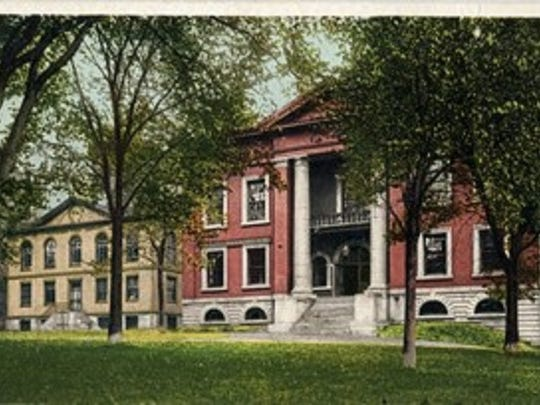 A vintage postcard showing a view of Burlington's first City Hall from City Hall Park with the building that originally housed the Fletcher Free Library on the left.