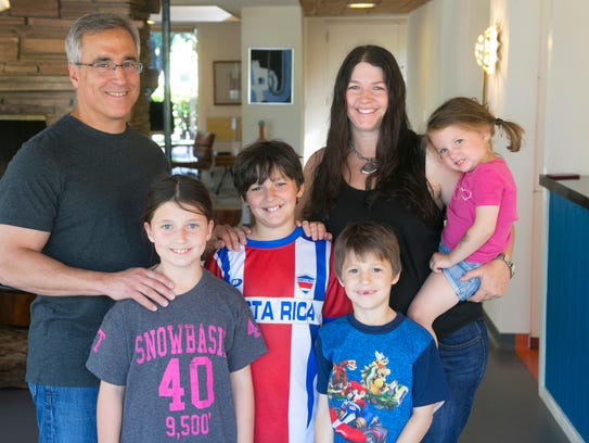 Bill and Bo Mostow stand with their children (from