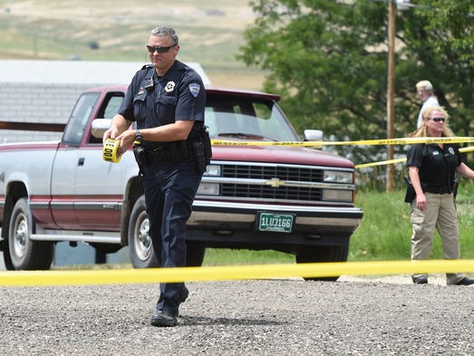 Fort Collins Police officers put up crime scene tap at the scene of a shooting Thursday July 24, 2014, on Thompson Drive in southwest Fort Collins.