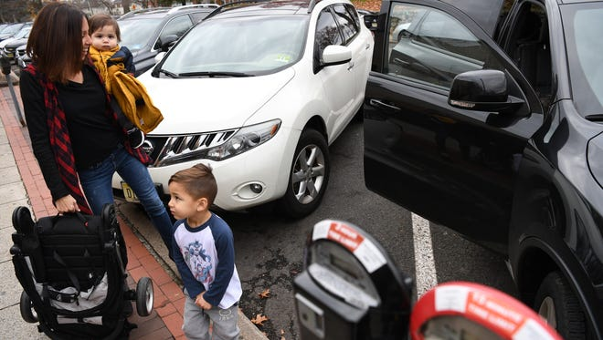 Danielle Gutierrez of Wyckoff getting ready to put her children into her vehicle on Saturday. She was parked in a metered 15-minute parking spot in downtown Ridgewood.