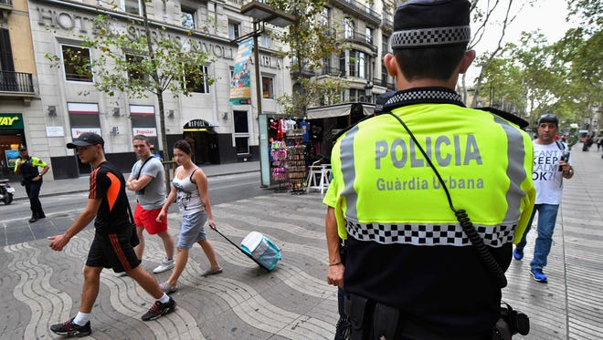 Police officers stand guard on the Las Ramblas in Barcelona just days after a van plowed into the crowd, killing at least 13 people and injuring over 100 others.