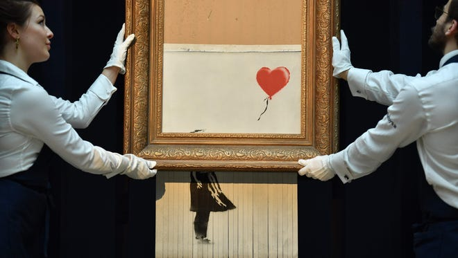 """Sotheby's employees hold the newly completed work by artist Banksy entitled """"Love is in the Bin,"""" a work that was created when the painting """"Girl with Balloon"""" was passed through a shredder in a surprise intervention by the artist, at Sotheby's auction house in London on October 12, 2018, following the work's sale. - The buyer of a work by street artist Banksy that was partially destroyed moments after it sold has gone through with the purchase, Sotheby's auction house said on October 11, 2018. The painting """"Girl with Balloon"""" was passed through a shredder hidden in the frame just after it went under the hammer last week for $1.4 million. Banksy's authentication body has renamed it """"Love is in the Bin."""""""