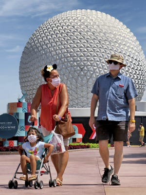 In this July 15, 2020 file photo, guests arrive to attend the official re-opening day of Epcot at Walt Disney World in Lake Buena Vista, Fla.