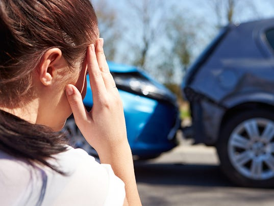 Driver looking at damaged cars after accident