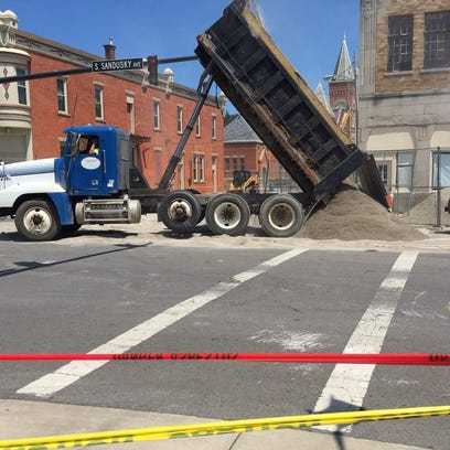 Workers dump sand in front of the Bucyrus Theater building