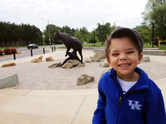 A young fan is all smiles in blue at the UK Wildcat statue in Lexington, Ky.