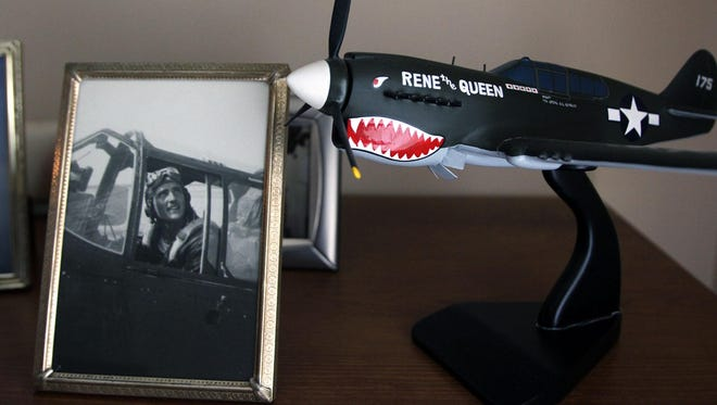 "A wartime photo of Donald Quigley sits next to a model of Quigley's P40 Warhawk, nicknamed ""Rene the Queen"" in honor of his wife, Irene."