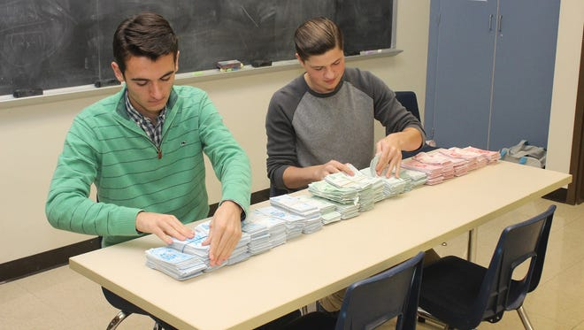 Christian Stahl, left, president of Elco High School's Interact Club, and club member Cody Good organize stacks of coupons that will be distributed to needy families in the Elco School District, who can exchange them for free turkeys at a local grocery store.