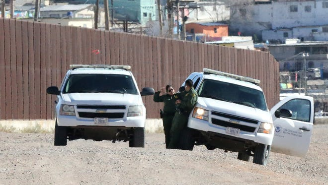 U.S. Border Patrol agents stand next to their vehicles Tuesday just beyond the border fence along West Paisano Drive.