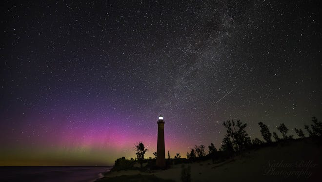 The northern lights shine over Little Sable Point Lighthouse near Silver Lake State Park in Michigan on July 16, 2017.