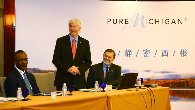 This photo released by the office of Michigan Gov. Rick Snyder shows Snyder, center, in Shanghai, China, on Tuesday, Nov. 25, 2014, during his trade mission to China.