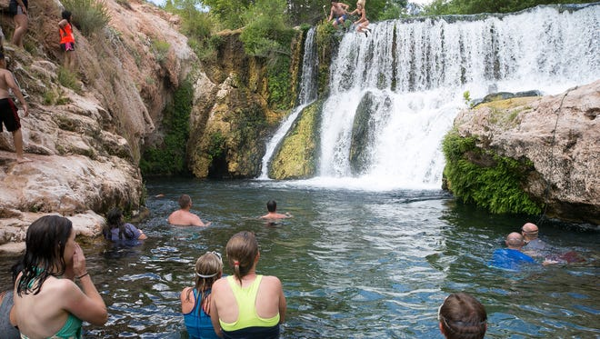 photos by Michael Schennum/The Republic  Swimmers watch as a couple jump off the old APS dam at Fossil Springs. The utility company allowed the water to flow again in 2005. Hikers watch as a couple jump off the old dam at Fossil Springs on Friday, June 12, 2015.