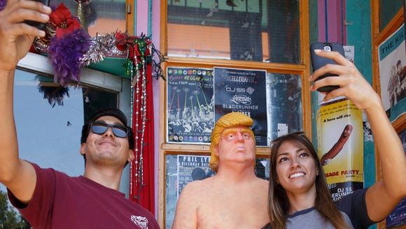 A naked Donald Trump statue gets the attention of passers-by