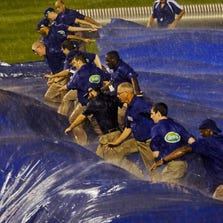 Grounds crew workers put the tarp down as rain delayed the Chicago Cubs game against the San Francisco Giants in the fifth inning at Wrigley Field.