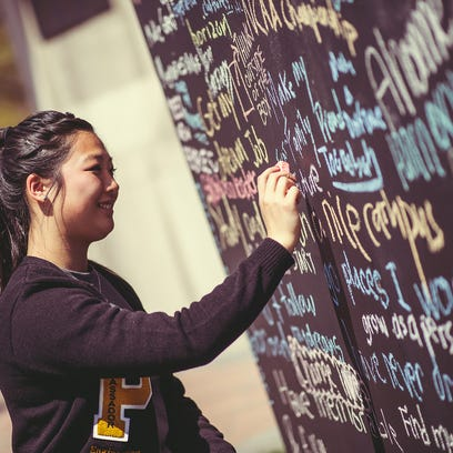 A student writes a message on a chalk wall as part