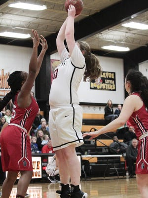 Holy Cross 6-foot-4 center Sid Thomas uses her height to make easy work of the St. Henry defense.