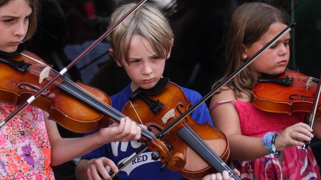 """Red Bank, NJ - Hannah Ludwikowski, Parker Ludwikowski, and Mae Woolley, students in Red Bank's school """"strings"""" program, perform on the sidewalk on Monmouth Street. The Red Bank Public School District recently cut its """"strings"""" program, and the Red Bank Borough of Education Foundation is attempting to raise $85,000 to reinstate the program."""