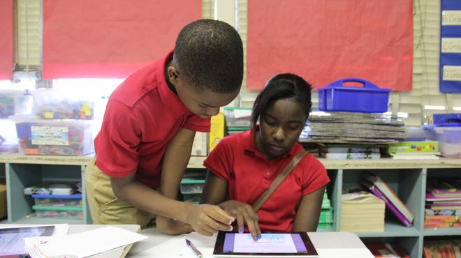 Kiara McPherson, seated, and Jeremiah Hilliard, two students at Em Boyd Elementary in Greenville, work on a science project. Students say they prefer the iPads to the desktop computers that they used to use in class. JACKIE MADER/THE HECHINGER REPORT