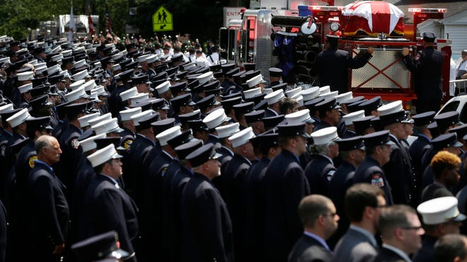 Firefighters and others line the street as a firetruck bearing the body of Lt. Gordon Ambelas leaves the funeral service Thursday in the New York City borough of Staten Island. Ambelas died searching for victims in a burning, cluttered Brooklyn high-rise apartment building.