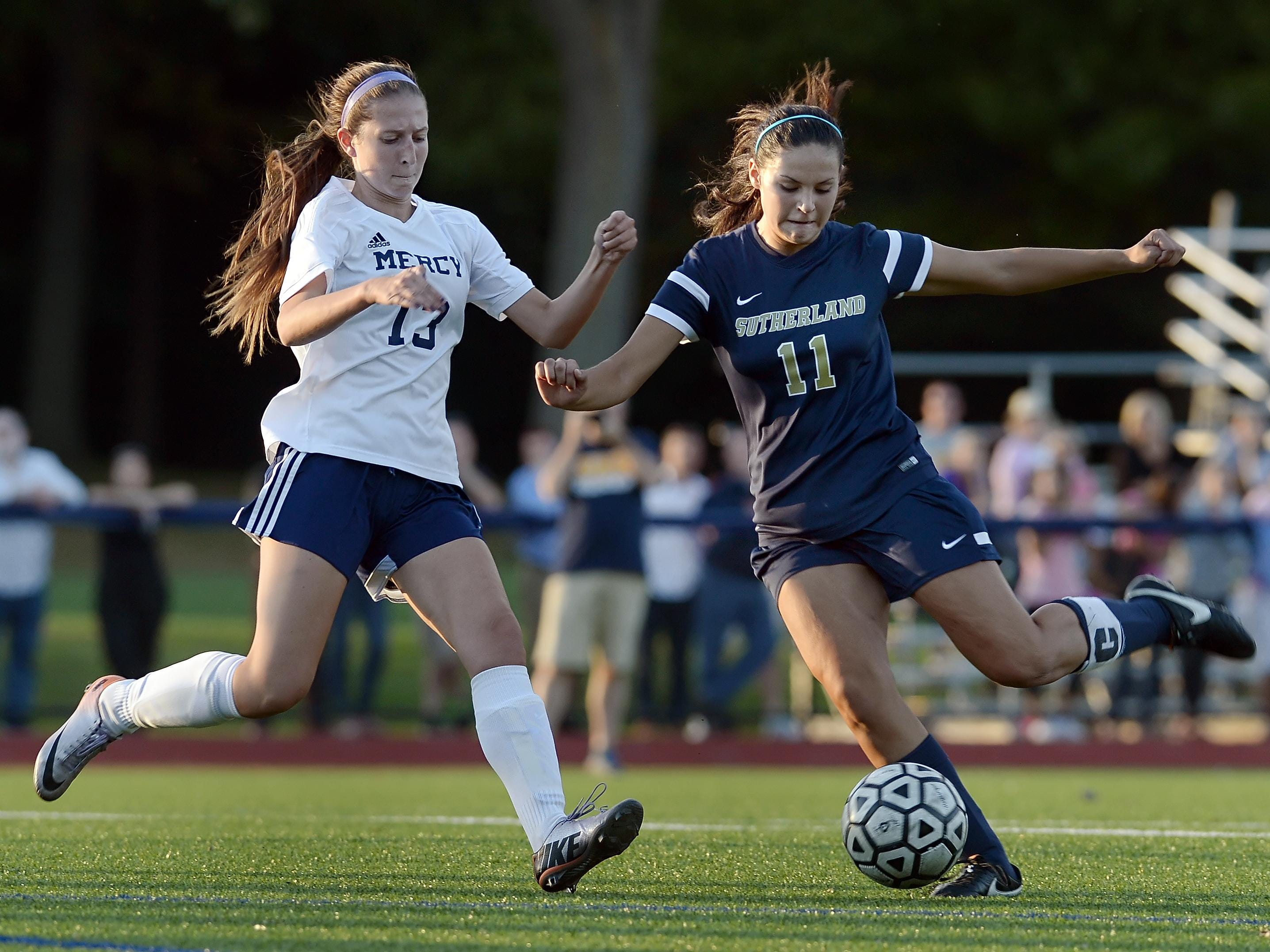 Pittsford Sutherland's Vicki Beatham, right, winds up a shot on goal while defended by Mercy's Kameron Baxter during a regular season game played at Our Lady of Mercy High School on Monday, October 12, 2015. Pittsford Sutherland beat Mercy 2-0.