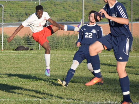 Riverheads' Josh Akinwumi follows through on a shot as Page County's Nathan Myers, center, and Ryan Taylor defend during the first half of their Shenandoah District boys soccer game on Monday, May 8, 2017, at Riverheads High School. The Gladiators won 2-0.