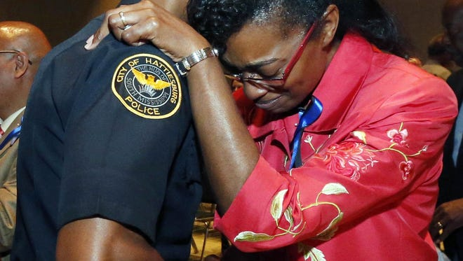 Youlander Ross, right, mother of slain Hattiesburg Police Officer Liquori Tate, is embraced by an officer after a memorial service in May. Tate and fellow Hattiesburg officer Benjamin Deen and Tate were gunned down May 9 following a traffic stop. It has been a really bad year for officers killed in the line of duty in Mississippi,Tennessee and Louisiana. Rogelio V. Solis/AP