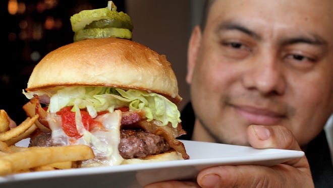 Chef Ruben Rodriguez shows off a Bru Burger with pepper bacon, taleggio cheese, tomato jam, mayo, lettuce and dill pickles at BRU Burger Bar (410 Mass Ave), one of 10 new restaurants on the Devour Downtown lineup.