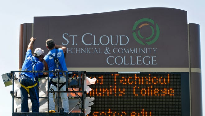Mark Frieler (left) and Tony Storms of Scenic Sign Corp. put up a new sign in front of St. Cloud Technical & Community College.