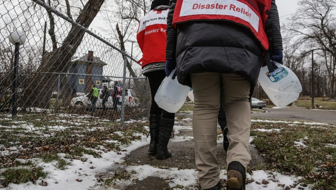 Members of the Red Cross carry jugs of purified water while going door-to-door delivering the free purified jugs of water and water filters to residents dealing with the water crisis on the the city's north side while helping the members of the Genesee County Sheriff's Department and the Sheriff's Reserve.