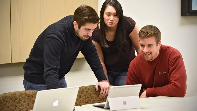 Garrett Shields, left, Sam Johnson, center and Dan Holthus gather in collaboration during an Upward Consulting group meeting Wednesday at St. Cloud State University. The group is part of the university's Industrial-Organizational Psychology program.