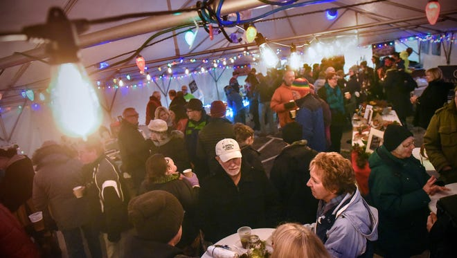 People enjoy hot drinks and food under the holiday lights in the main tent during the St. Cloud Weihnachtsmarkt Thursday, Dec. 7, near the River's Edge Convention Center.