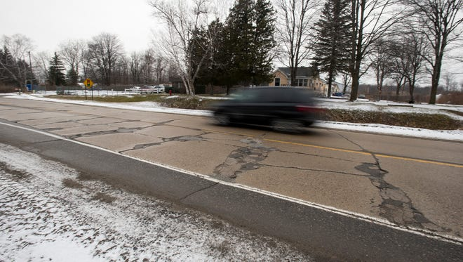 A van drives past cracks in Dove Road just east of Range Road in Port Huron Dec. 22.  The section of Dove Road between Range and Michigan Roads is getting state dollars for a resurfacing project through the St. Clair County Road Commission.