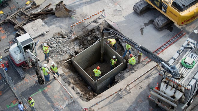 Crews make repairs to a sinkhole threat at the corners of Maryland and Illinois Streets, Indianapolis, July 19, 2018. This is the second major street problem in downtown Indy in the past month.