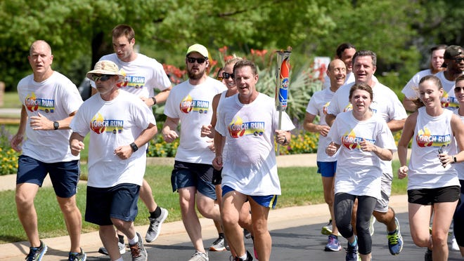 Jim Rothwell, director of marketing for Shelter Insurance, holds the Show-Me State Games torch as he runs with fellow employees in 2018 to the Shelter Insurance office on West Ash Street in Columbia.