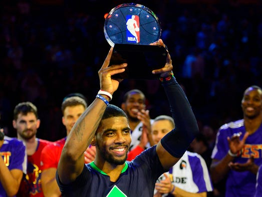 Eastern Conference guard Kyrie Irving celebrates with the MVP trophy after the 2014 NBA All-Star Game.