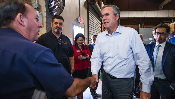 Gov. Jeb Bush, right, greets Four Peak Brewery co-owner