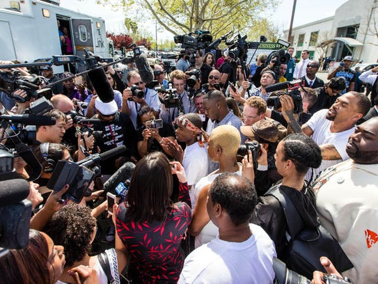 Stevante Clark tis surrounded by media after the funeral