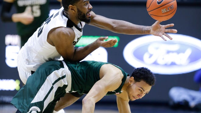 Purdue guard Rapheal Davis (35), top, attempts to pick up a loose ball over Michigan State guard Bryn Forbes (5) in the second half of MSU's 82-81 overtime loss Tuesday in West Lafayette, Ind.