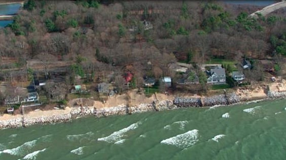 An aerial view of rock walls lining beaches next to homes along Lake Michigan in Ottawa County in November 2020. High water levels have threatened roadways in Michigan for the past two years, and a group which represents Michigan's 83 counties is calling on Michigan's government to pass funding to address the state's roads and bridges.