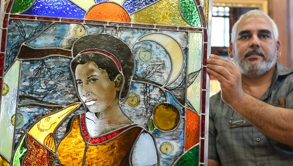 Cuban artist Esteban Rodriguez holds his newly completed