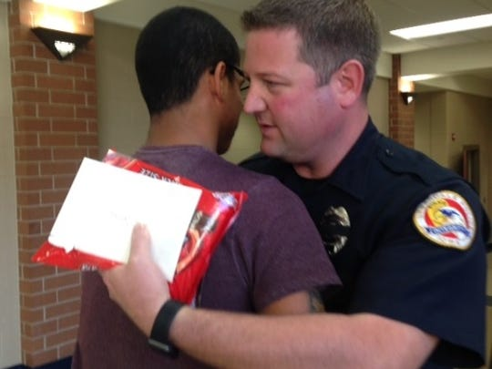 Urbandale senior Logan Samuels hugs Matt Flattery, a school resource officer, mid-morning. Samuels had given Flattery a card and chocolate earlier in the day.