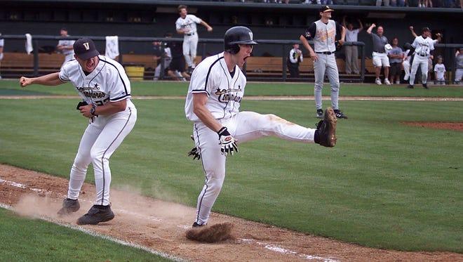 Vanderbilt's Worth Scott, center, and assistant coach Erik Bakich, left, celebrate as Scott's hit flies over the first baseline fence for the winning run. Tennessee's pitcher Luke Hochevar watches the Vols season end with the Vanderbilt home run.