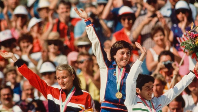 Joan Benoit Samuelson, center, waves to the crowd after winning the gold medal in the women's marathon at the 1984 Olympics.