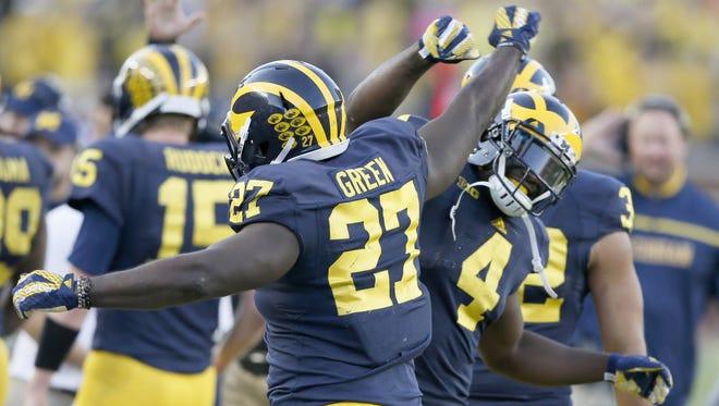 Michigan's Derrick Green (27) celebrates with De'Veon Smith after Green scored on a 4-yard run against Northwestern on Saturday, Oct. 10, 2015, at Michigan Stadium in Ann Arbor.
