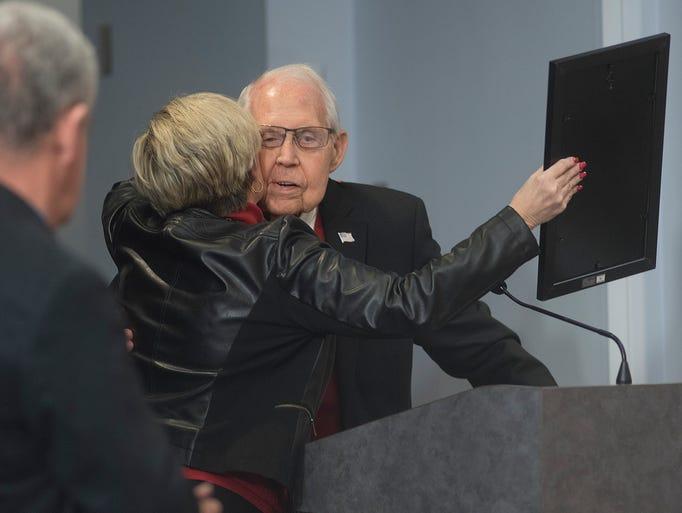 Maureen Miller Brosnan hugs Joe Taylor as he is honored